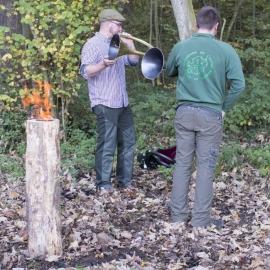 Traqueur rendant hommage au gibier à l'aide d'un cor de chasse.